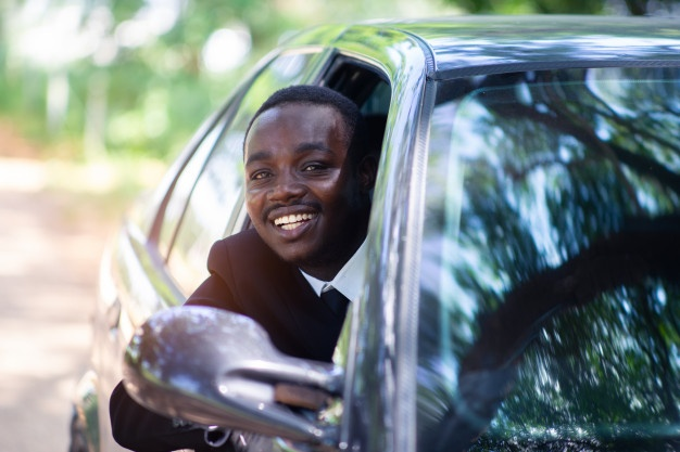 business-man-driving-smiling-while-sitting-car-with-open-front-window_73622-273